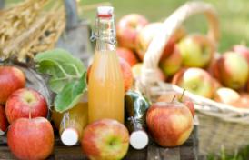 Äpfel und eine Flasche Apfelsaft auf einem Holztisch.